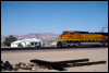 Dash 9-44CW 4511 rolls by Desert Market and railroad ties at Daggett, CA, 1999