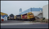 GP30 2750 and friends negotiate their way through the business park at Miramar, CA, in 1989.  The local is about to cross Distribution Avenue to spot RBL cars at a nearby industry. The building to the left with the colorful striping is Kid's Warehouse.