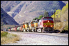 Dash 9 768 leads at the Swarthout Canyon Road xing in Cajon Pass, 2000