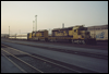 SD40-2s 5107 and 5119 idle with a pair of passenger cars as the sun sets at San Bernardino, CA, 1991